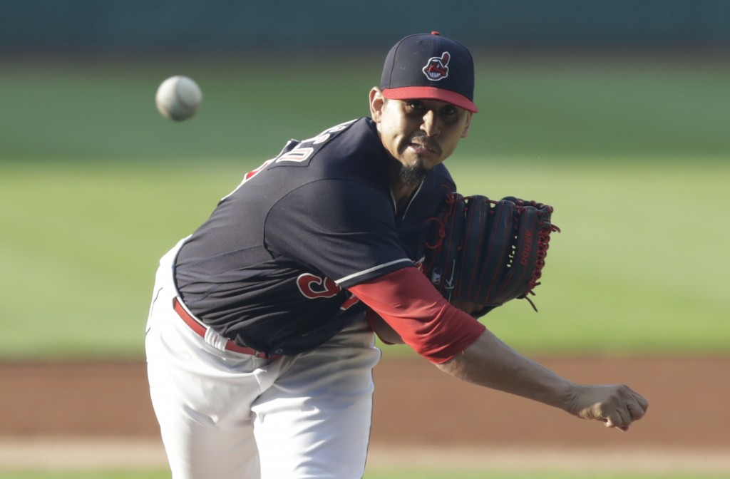 Cleveland Indians starting pitcher Carlos Carrasco watches a throw during the first inning of the team's baseball game against the Cincinnati Reds, We