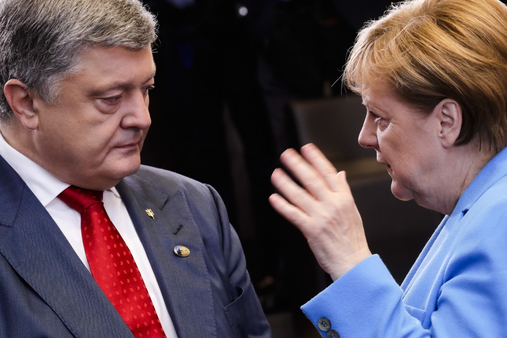 CORRECTS DATE - German Chancellor Angela Merkel, right, and Ukraine's President Petro Poroshenko, left, talk together, prior to a working session duri