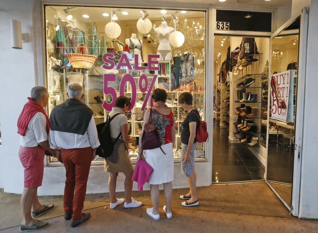 FILE- In this April 26, 2017, file photo, window shoppers look into a store on Miami Beach, Florida's Lincoln Road. As Amazon gears up for its Prime D