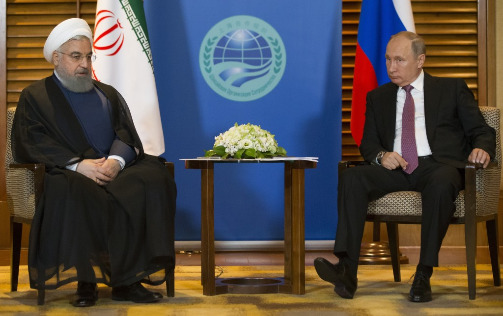 FILE - In this June 9, 2018 file photo, Russian President Vladimir Putin, right, speaks to Iranian President Hassan Rouhani during their meeting in Qi