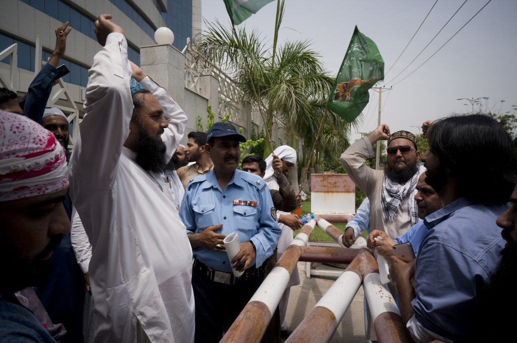 In this Monday, July 9, 2018 photo, supporters of Pakistani radical, religious and sectarian groups protest outside the office of the Pakistan Electro