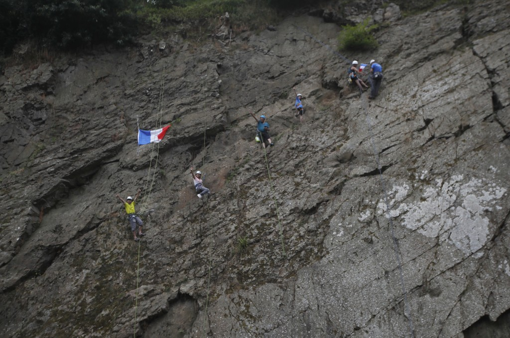 Rock climbers wait for the riders to pass during the seventh stage of the Tour de France cycling race over 231 kilometers (143.5 miles) with start in