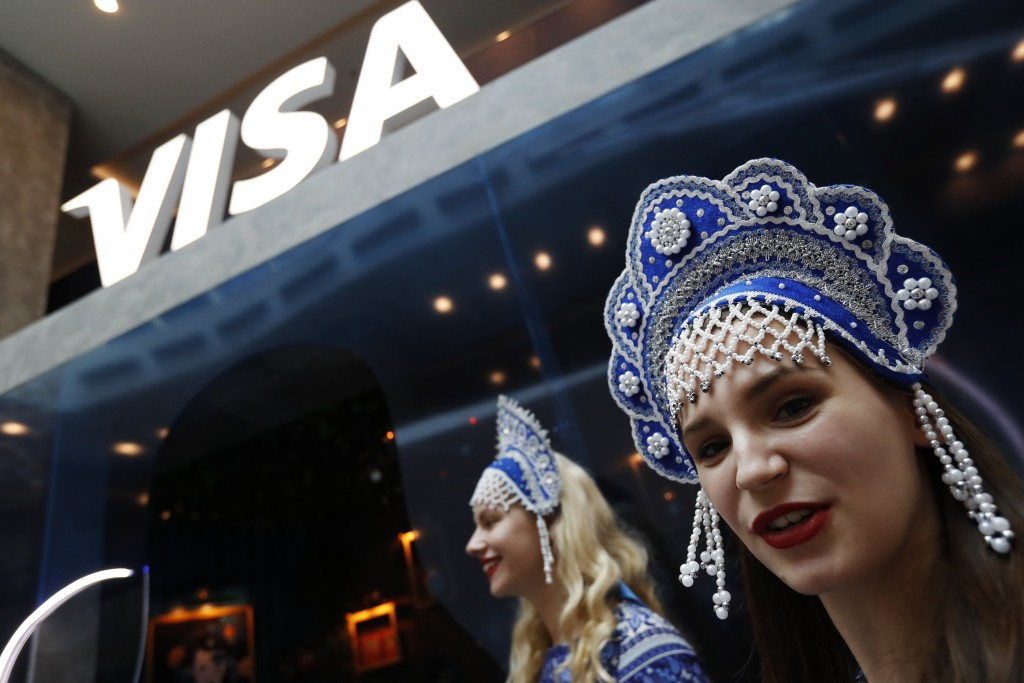 In this July 5, 2018 photo, women wearing traditional head dresses wait to greet Visa cardholders who won trips to the 2018 soccer World Cup, at the M