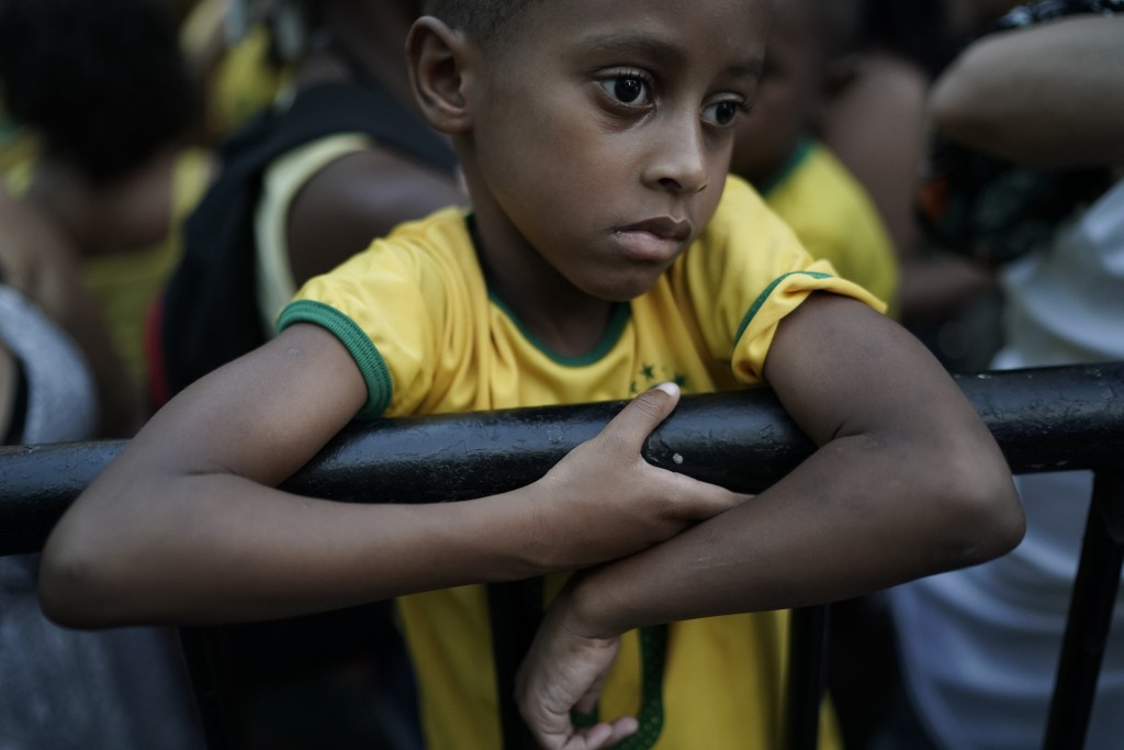 In this July 6, 2018 photo, a young Brazil soccer fan stands dejectedly on a railing after watching his team loose in a live broadcast of the World Cu