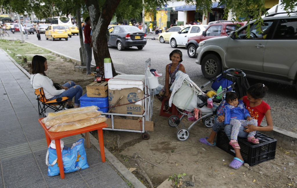 In this June 28, 2018 photo, Venezuelan migrant Maria Fuentes, center, sits with her daughter, left, and two granddaughters as she sells snacks from t