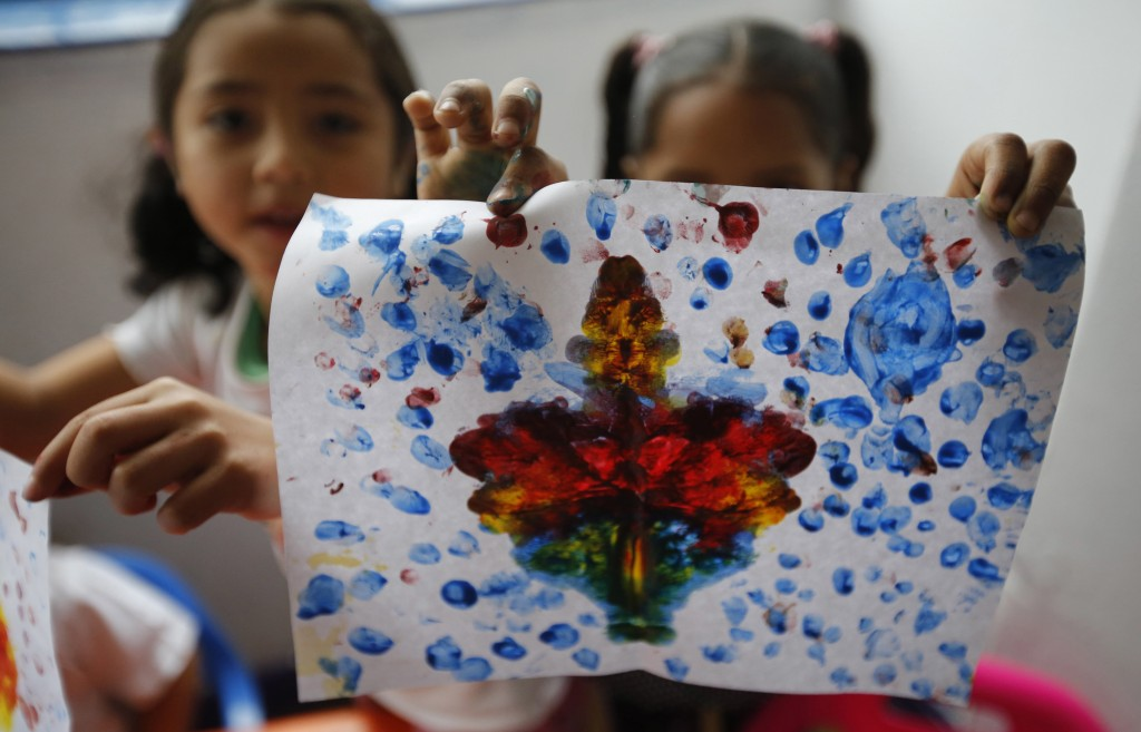 In this July 4, 2018 photo, a Venezuelan migrant girl shows off her painting at the child development center Social Foundation Grow where working Vene