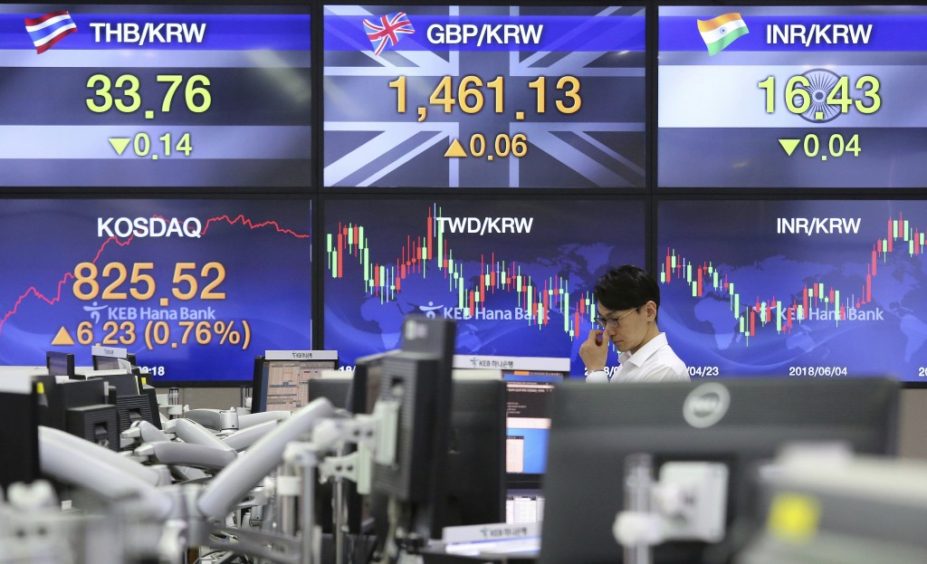 A currency trader watches monitors at the foreign exchange dealing room of the KEB Hana Bank headquarters in Seoul, South Korea, Friday, July 13, 2018...
