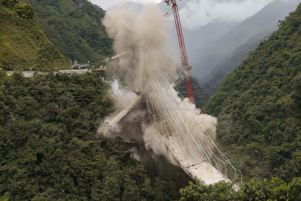 In this July 11, 2018 photo, a partially-built suspension bridge is demolished by engineers in Chirajara, Colombia. One part of the bridge collapsed i