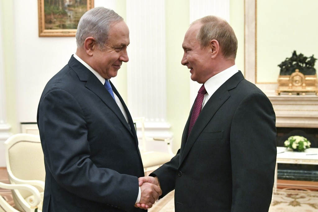 FILE - In this Wednesday, July 11, 2018 file photo, Russian President Vladimir Putin, right, shakes hands with Israeli Prime Minister Benjamin Netanya