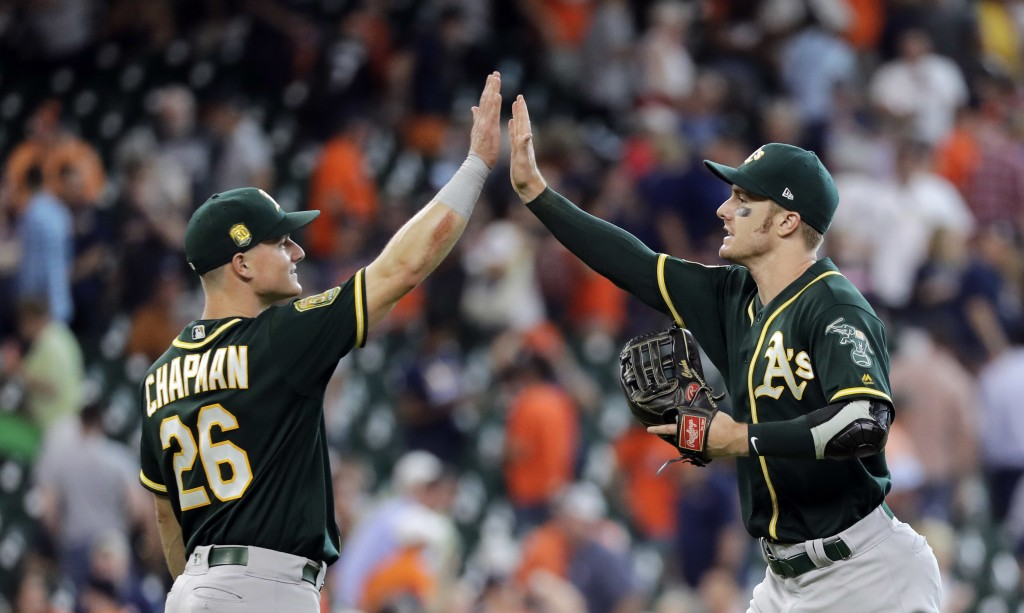 Oakland Athletics' Matt Chapman (26) and Mark Canha celebrate after a baseball game against the Houston Astros Thursday, July 12, 2018, in Houston. Th