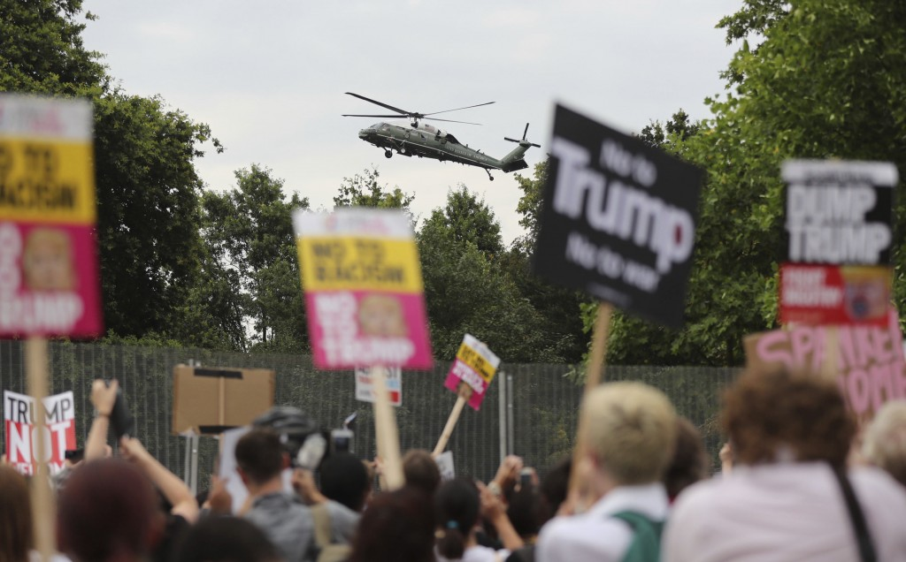 A US presidential helicopter lands in the grounds of the US ambassador residence in Regent's Park, London, while demonstrators protest against the vis