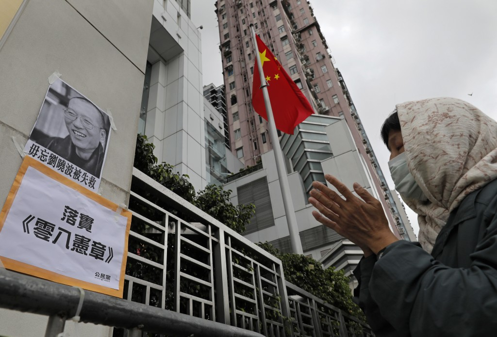 A protester pays respect to late Chinese Nobel Peace laureate Liu Xiaobo during a protest outside the Chinese liaison office in Hong Kong, Friday, Jul