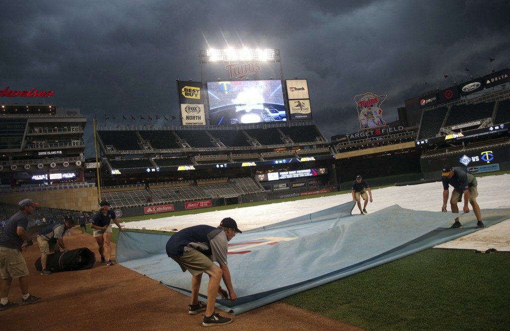 Grounds crew workers cover the field as storm clouds arrive bringing heavy rain before a baseball game between the Minnesota Twins and the Tampa Bay R