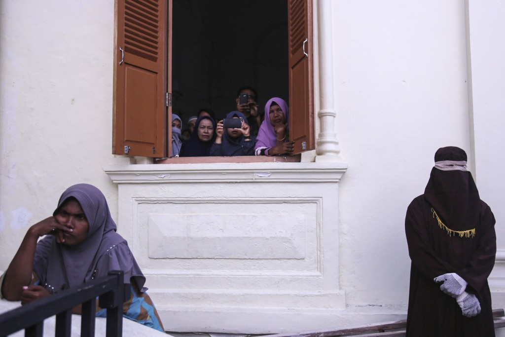 A Shariah law official, right, waits for his turn to deliver caning to people convicted of violating sharia law as Acehnese women watch during a publi