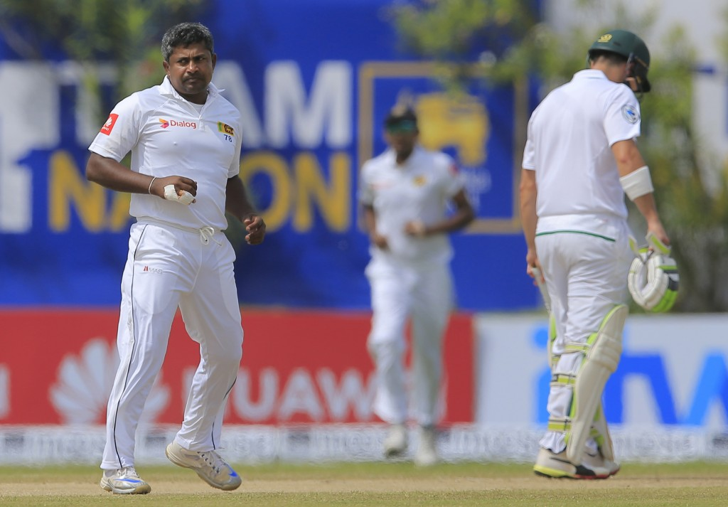 Sri Lanka's Rangana Herath, left, celebrates the dismissal of of South Africa's Keshav Maharaj during the second day of their first test cricket match
