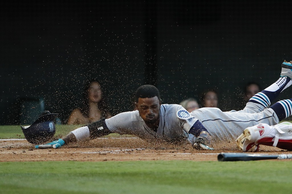 Seattle Mariners' Dee Gordon scores on a single by Kyle Seager during the first inning of a baseball game against the Los Angeles Angels, Thursday, Ju