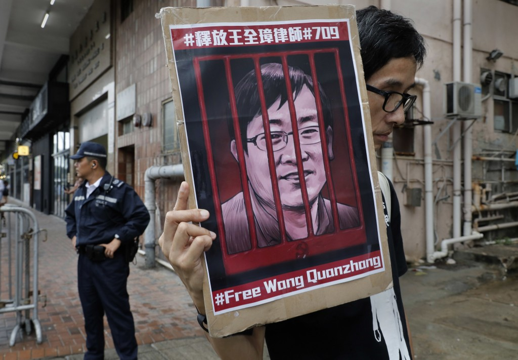 A protester holds a picture of imprisoned and prominent Chinese human rights lawyer Wang Quanzhang during a protest outside the Chinese liaison office