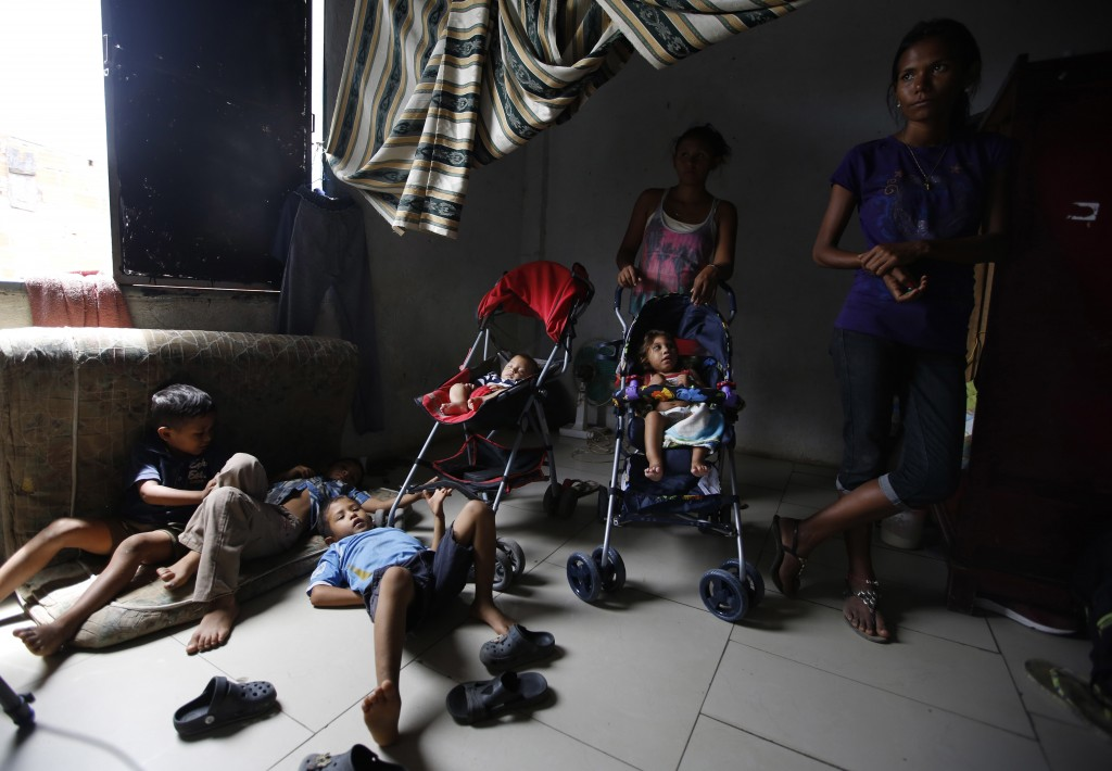 In this June 27, 2018 photo, Venezuelan children are watched over by a few of their mothers while others work, inside a sparsely furnished home shared