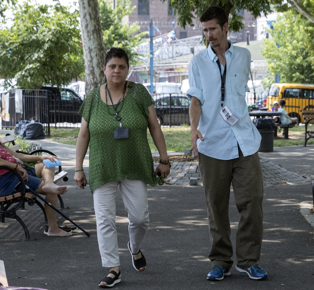 In this Tuesday, July 3, 2018, photo, VOCAL-NY harm reduction coordinator Paula Santiago, left, and peer educator Chris Marshal walk through a park ne