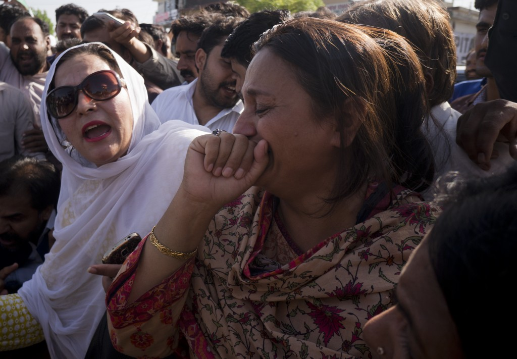 In this Friday, July 6, 2018 photo, supporters of former Pakistani Prime Minister Nawaz Sharif react outside a court following a ruling against him th