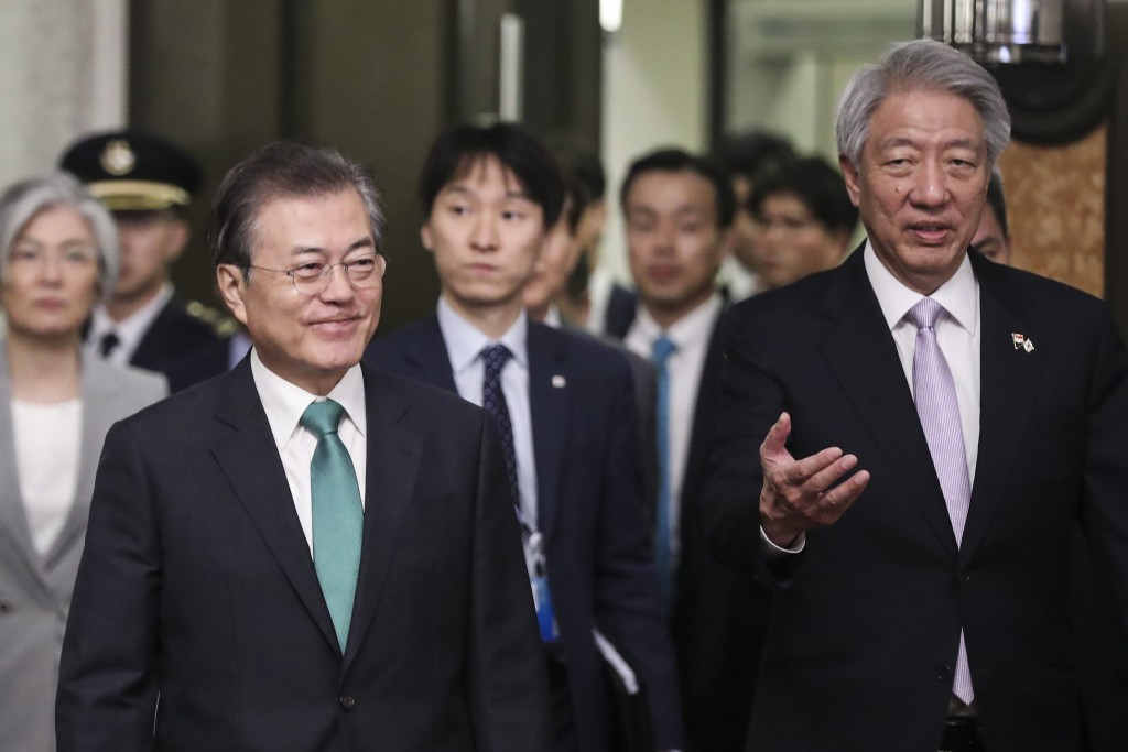 South Korea's President Moon Jae-in, left, arrives with Singapore's Deputy Prime Minister Teo Chee Hean, right, for the 42nd Singapore Lecture organiz