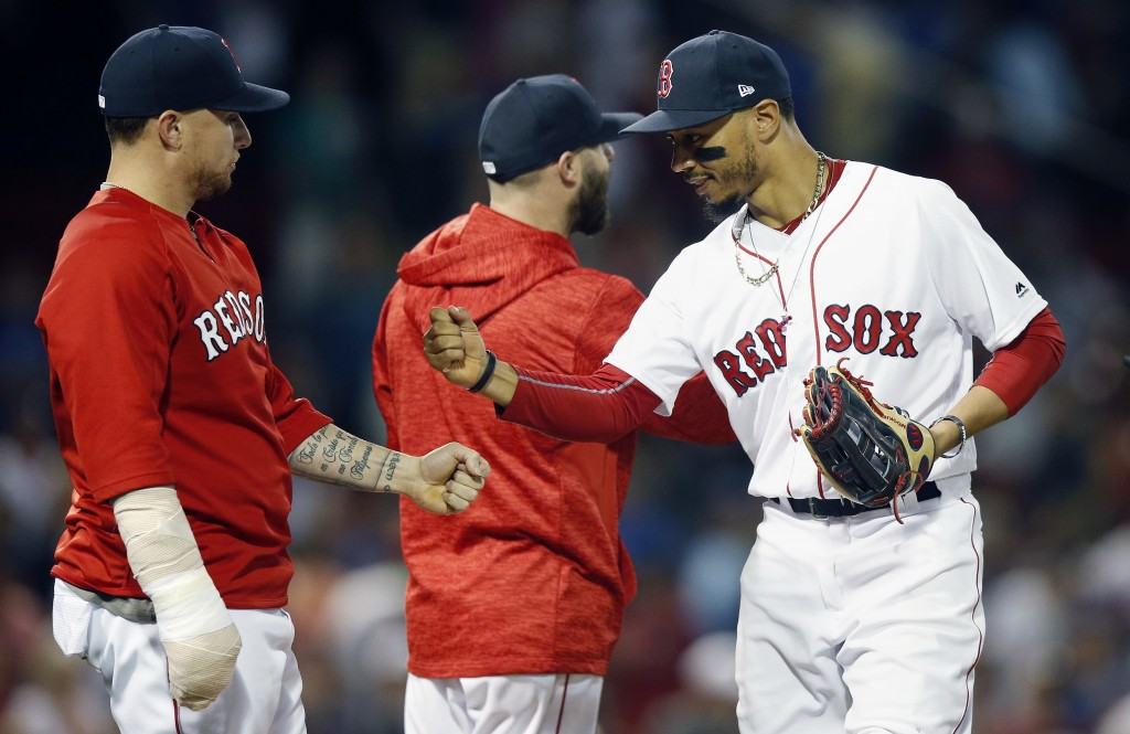 Boston Red Sox's Mookie Betts, right, celebrates with Christian Vazquez, left, after the Red Sox defeated the Toronto Blue Jays 6-4 during a baseball