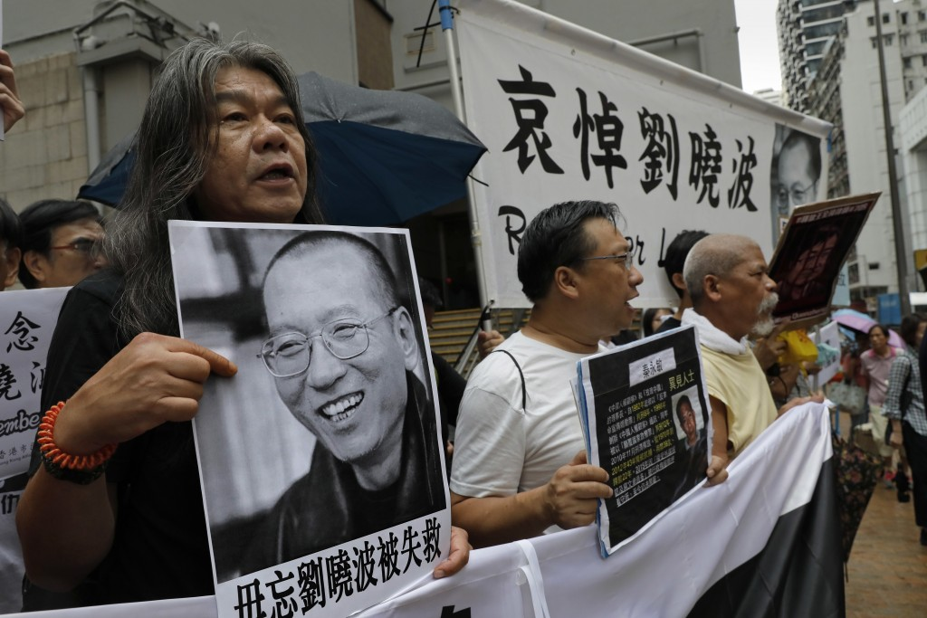 Protesters hold pictures of late Chinese Nobel Peace laureate Liu Xiaobo during a protest outside the Chinese liaison office in Hong Kong, Friday, Jul