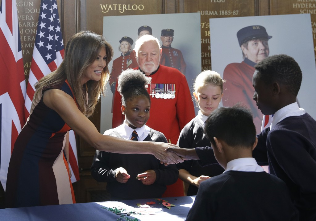 "U.S. First Lady Melania Trump shakes hands with a schoolboy as she helps children to make poppies as she meets British military veterans known as ""Che"