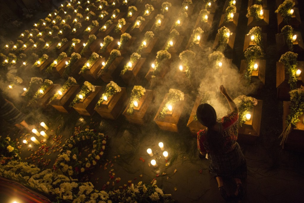 In this June 20, 2018 photo, a woman spreads incense over coffins holding the remains of 172 unidentified people who were discovered buried at what on