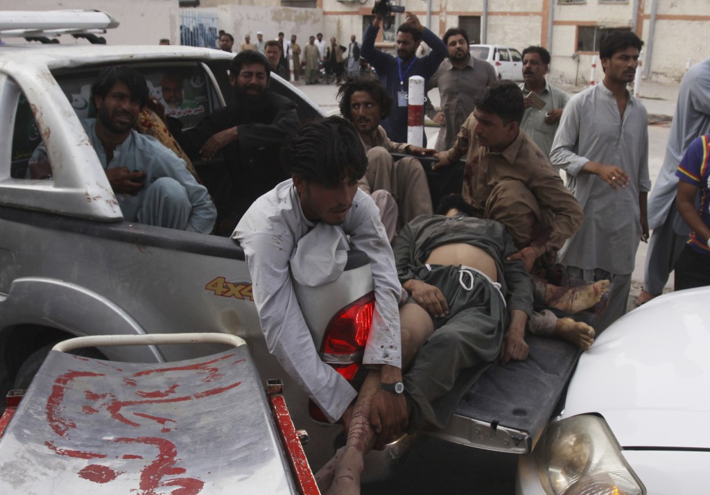 People shift injured persons to a hospital in Quetta, Pakistan, Friday, July 13, 2018. Underscoring the security threat, two bombs exploded Friday kil