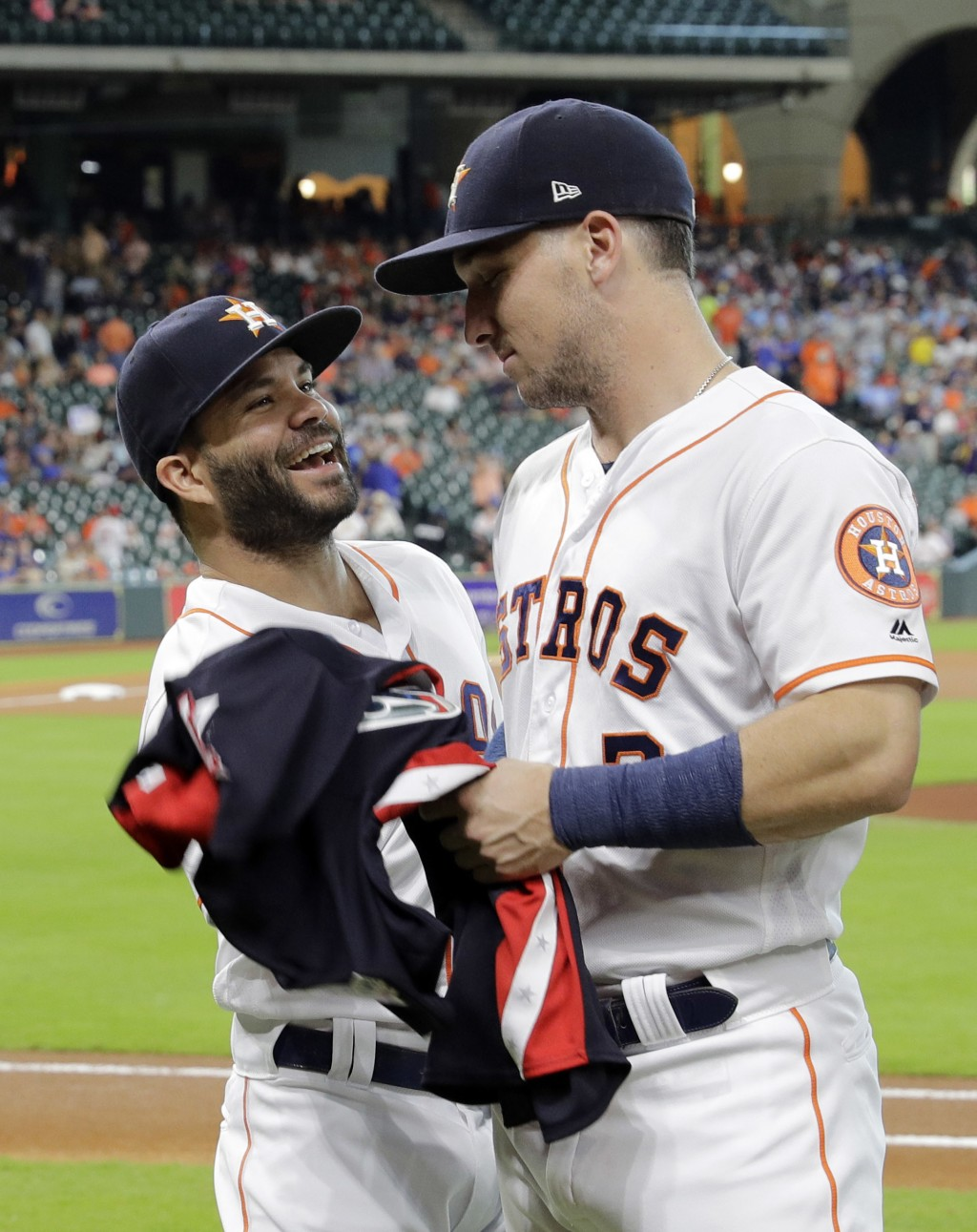 Houston Astros' Jose Altuve, left, jokes with Alex Bregman after they were presented their All-Star jerseys before a baseball game against the Oakland...