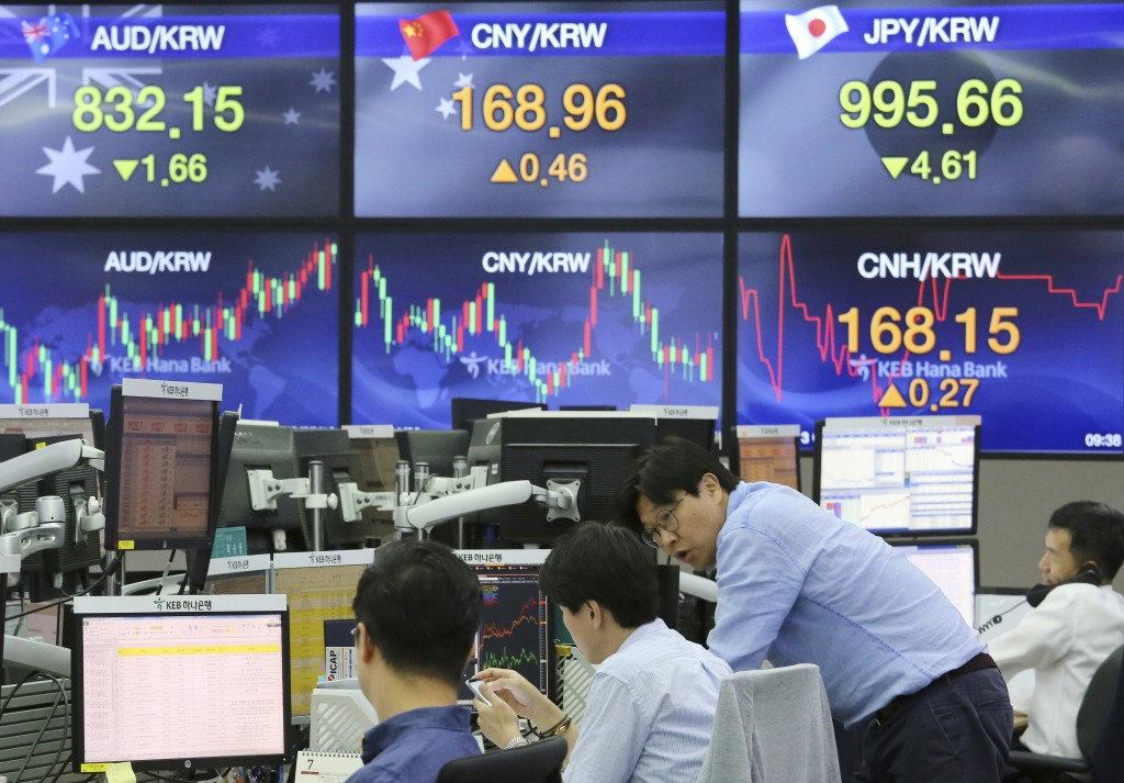 Currency traders work at the foreign exchange dealing room of the KEB Hana Bank headquarters in Seoul, South Korea, Friday, July 13, 2018. Asian stock