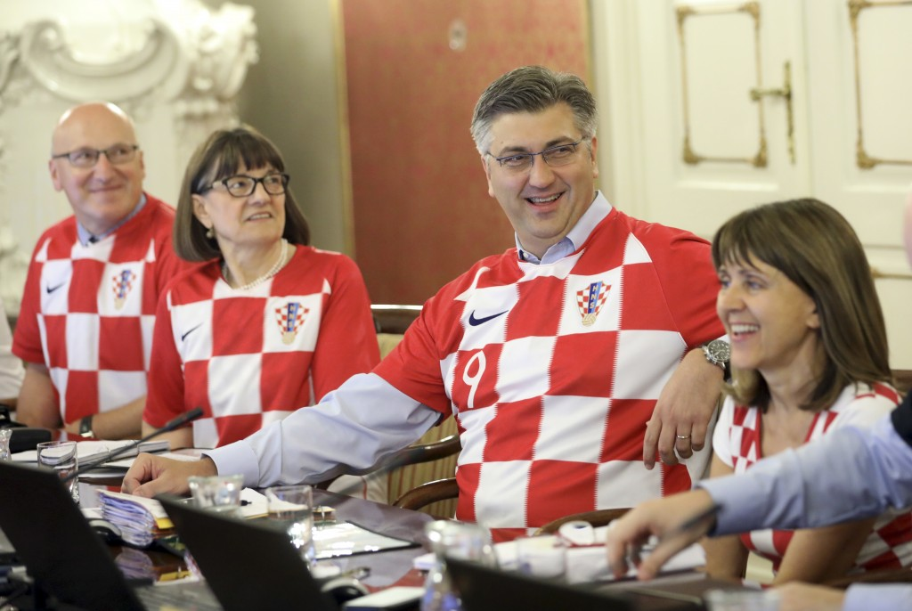 Croatia's Prime Minister Andrej Plenkovic, center, sits between ministers wearing Croatian national soccer team jerseys during during a government ses