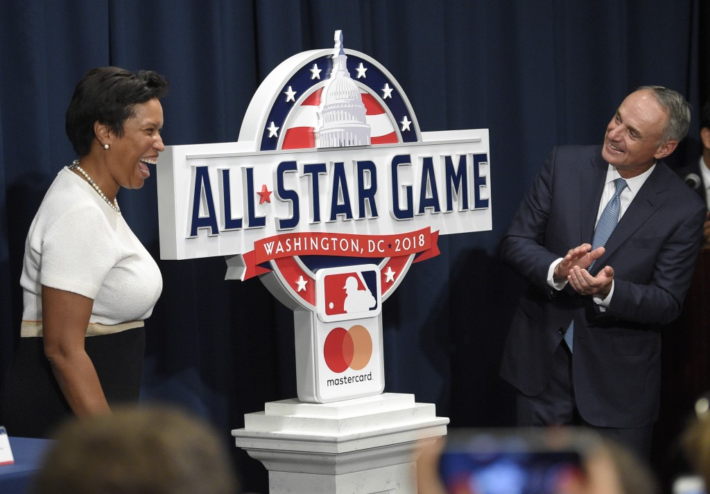 FILE - In this July 26, 2017, file photo, Muriel Bowser, left, Mayor of the District of Columbia, and Rob Manfred, Commissioner of Baseball, react at