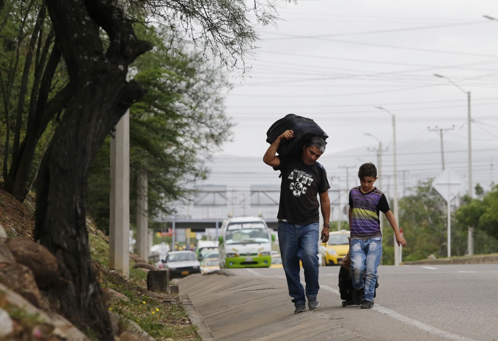 In this June 28, 2018 photo, Venezuelan father Darwin Zapata walks with his 12-year-old son along a highway in Cucuta, Colombia, as they make their wa