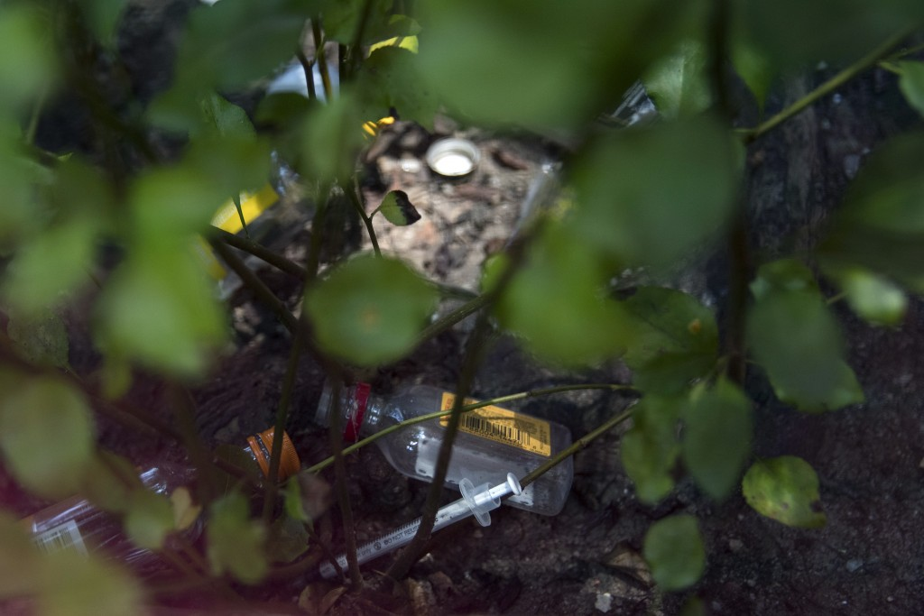 In this Tuesday, July 3, 2018, photo, a used syringe and empty liquor bottles are discarded in the bed of a sidewalk tree near VOCAL-NY headquarters i