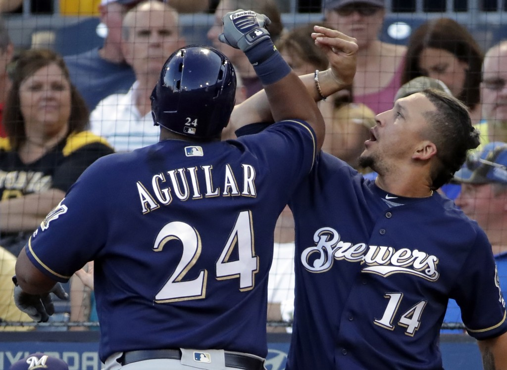 Milwaukee Brewers' Jesus Aguilar (24) celebrates with Hernan Perez as he returns to the dugout after hitting a solo home run off Pittsburgh Pirates st