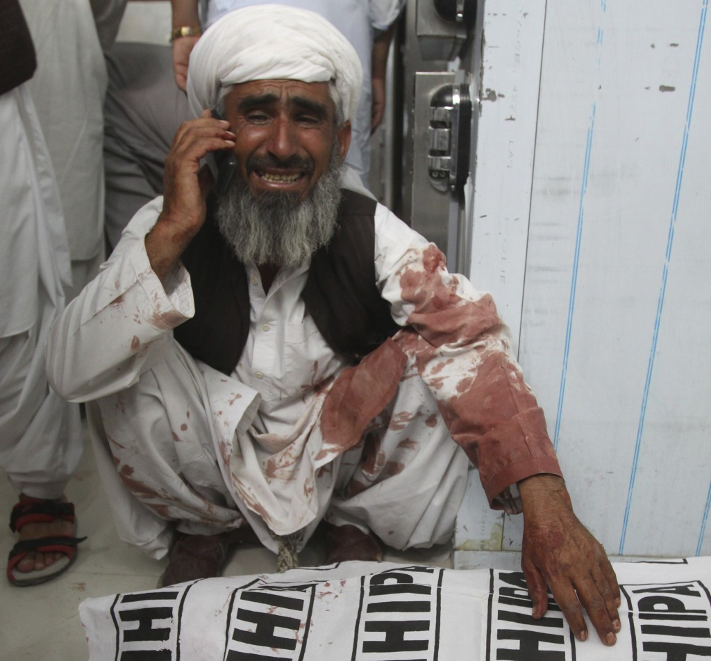 A man talks on a phone sitting next to a body of his family member killed in a bomb attack, in Quetta, Pakistan, Friday, July 13, 2018. Underscoring t