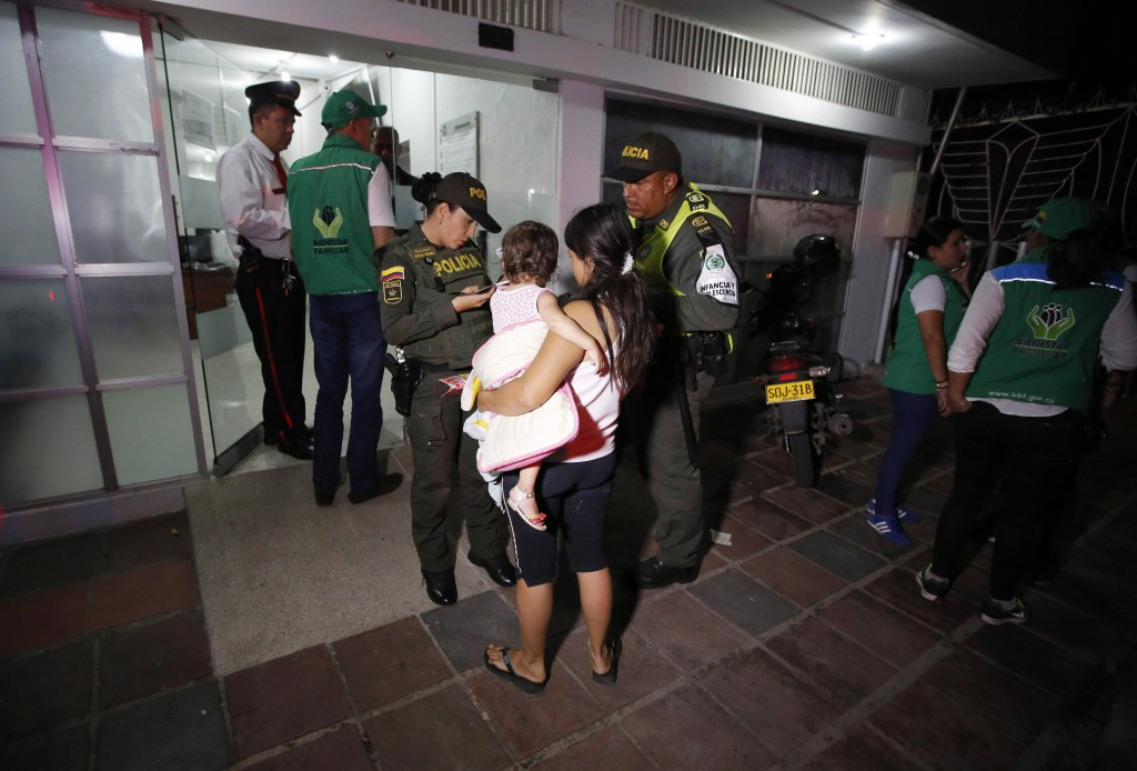 In this June 26, 2018 photo, police attend 17-year-old Venezuelan Eliusmar Guerrero and her 1 ½-year-old daughter at a child welfare office where she