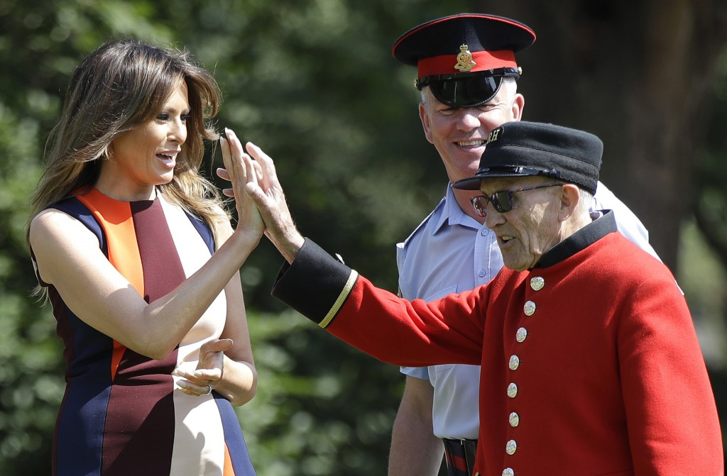 "U.S. First Lady Melania Trump high-fives with a British military veteran known as a ""Chelsea Pensioner"" during a game of bowls at The Royal Hospital C"