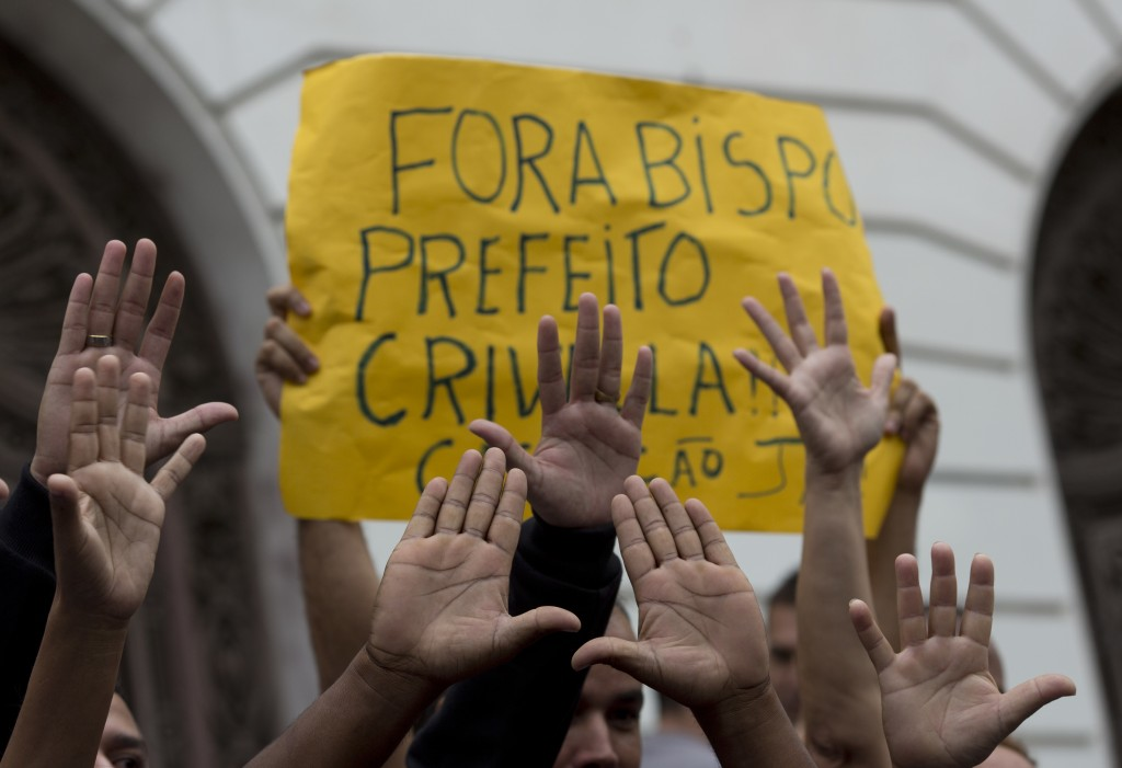 "Supporters of Rio Mayor Marcelo Crivella raise their hands in front of a sign that reads in Portuguese: ""Out Bishop, Mayor Crivella, Impeachment now"""