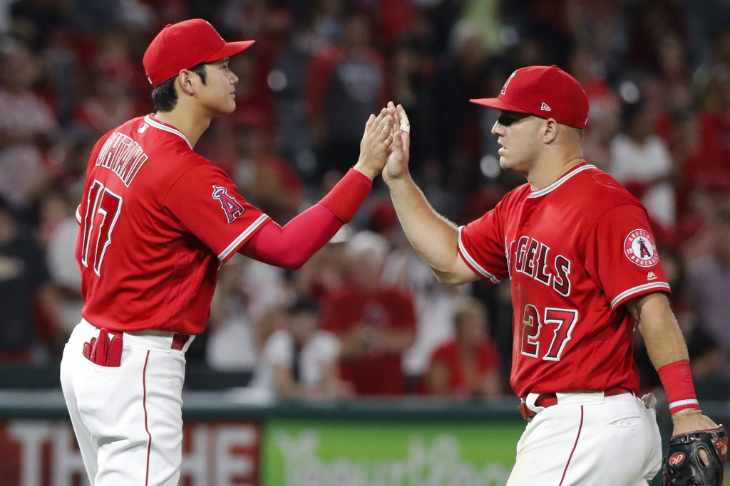 Los Angeles Angels' Shohei Ohtani, left, of Japan, and Mike Trout celebrate the team's 11-2 win against the Seattle Mariners in a baseball game, Thurs