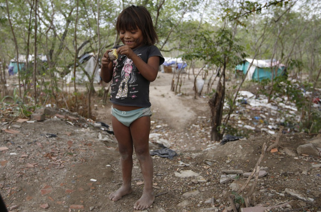 In this June 26, 2018 photo, a barefoot Venezuelan Yupka indigenous girl picks the skin off a cooked potato before eating it at her community's camp s