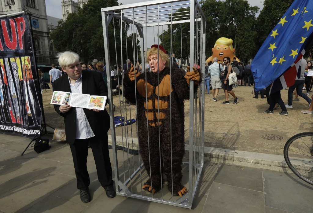 A lookalike of former British Foreign Minister Boris Johnson stands next to a person in a cage wearing a money suit and a mask of U.S. President Donal