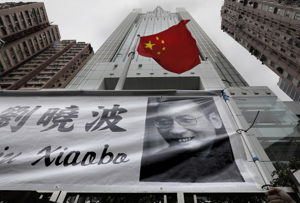 A banner of with picture of late Chinese Nobel Peace laureate Liu Xiaobo is displayed during a protest outside the Chinese liaison office in Hong Kong