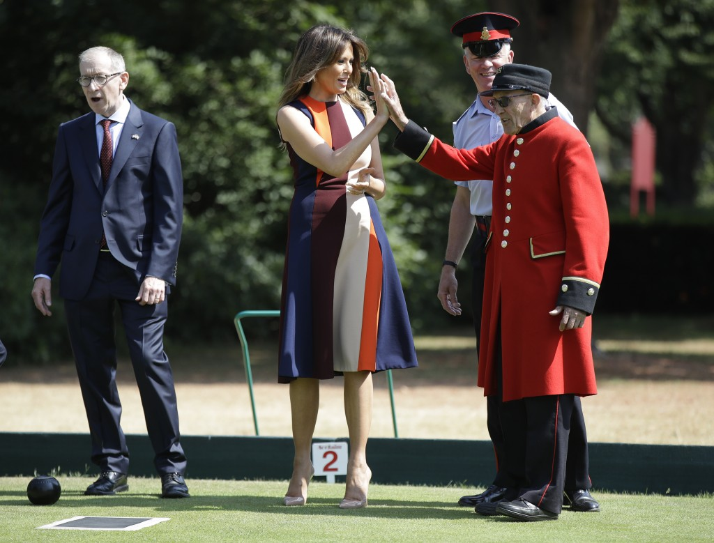 "U.S. First Lady Melania Trump high-fives with a British military veteran known as a ""Chelsea Pensioner"" during a game of bowls with Philip May, the hu"