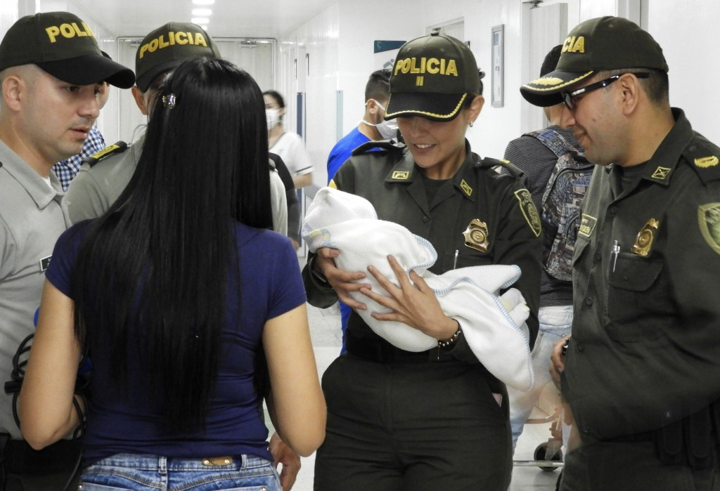 In this June 1, 2018 photo provided by the Colombia National Police, officers arrive to a hospital with an abandoned newborn baby girl who was discove