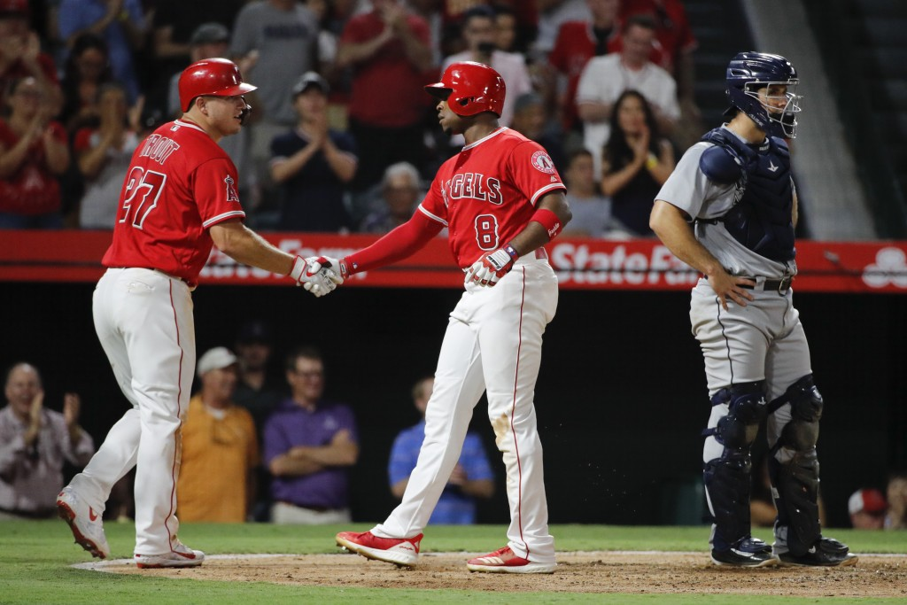 Los Angeles Angels' Justin Upton, center, celebrates his three-run home run with Mike Trout as Seattle Mariners catcher David Freitas stands near the