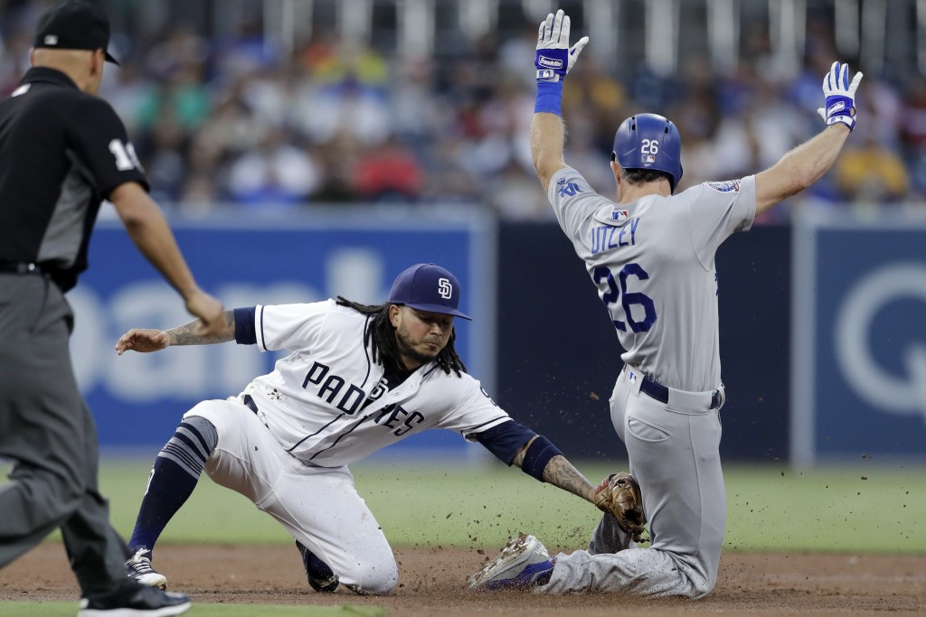 San Diego Padres shortstop Freddy Galvis, left, tags out the Los Angeles Dodgers' Chase Utley on a steal attempt during the third inning of a baseball