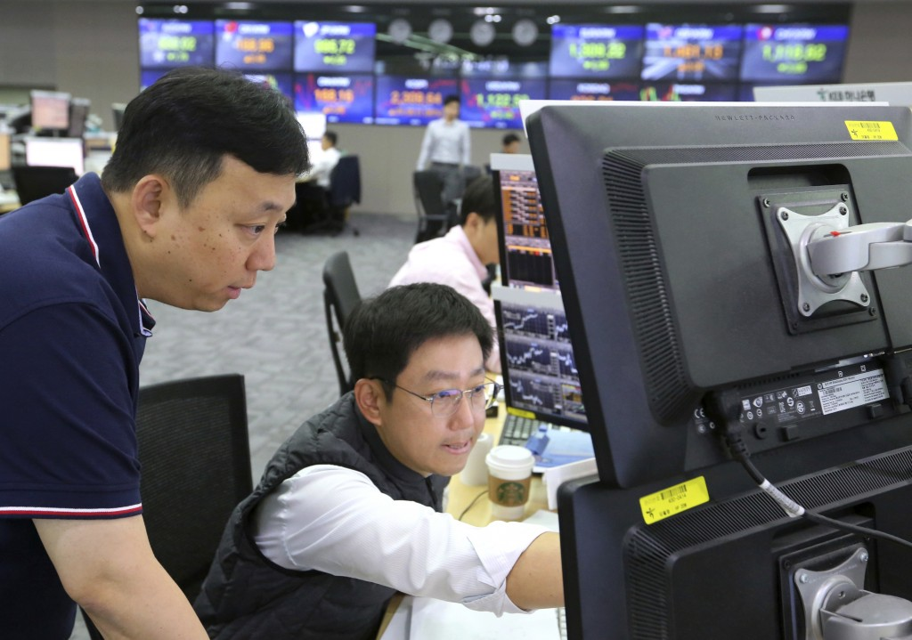 Currency traders watch monitors at the foreign exchange dealing room of the KEB Hana Bank headquarters in Seoul, South Korea, Friday, July 13, 2018. A